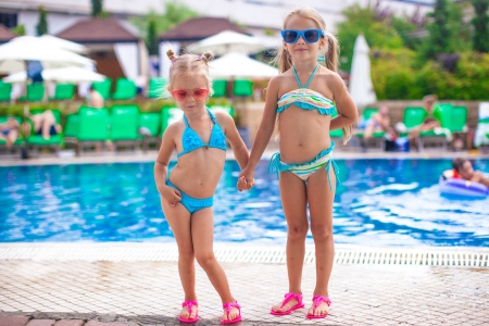 Two cute little sisters standing together near swimming pool