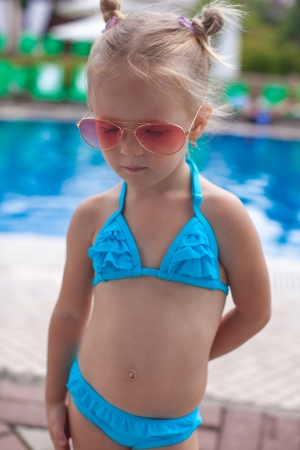 Cute little girl standing alone near swimming pool photo