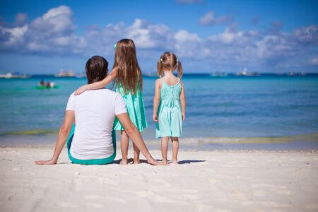 happines: Back view of happy father with his two daughters on tropical beach vacation Stock Photo