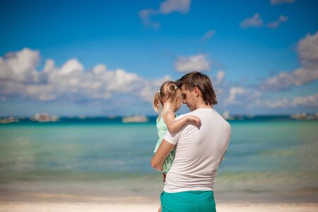 Portrait of a little girl hugging with dad on the beach photo