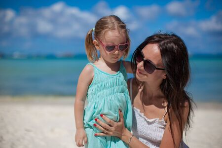 happines: Portrait of young beautiful mother and her adorable little daughter at tropical beach