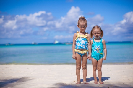 Two little sisters in nice swimsuits at tropical beach in Philippines photo