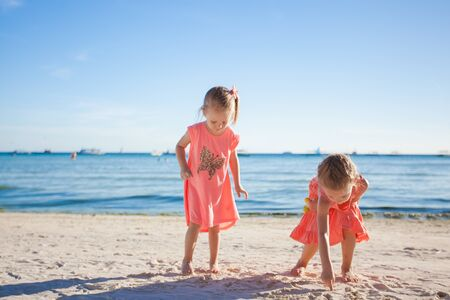 youngbaby: Two little sisters playing together on the white beach Stock Photo