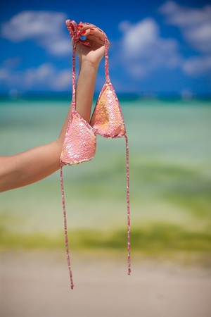 Womans hand holding pink bra background the sea photo