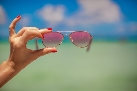 Womans hand holding pink sunglasses on tropical beach background the sea photo