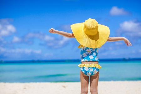 swimsuits: Rear view of baby girl in big hat looking at the sea on white sand beach