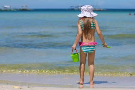Adorable little girl in beautiful swimsuit walking at tropical photo