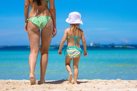 Mother and her little daughter walking at tropical beach photo
