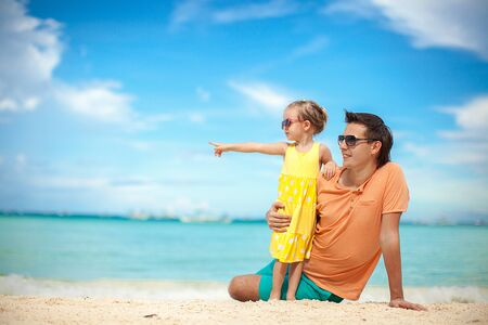 Young father and his adorable little daughter have fun at beach photo