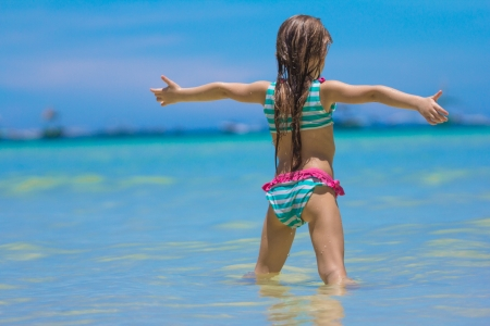 Beautiful little girl spread her arms standing at the beach photo