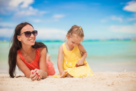 happines: Young mother and her little daughter lying at tropical beach