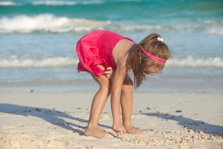 little cute girl draws on the white sand at tropical beach photo