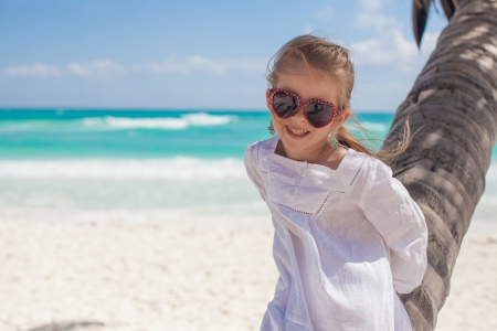 Closeup of smiling girl sitting on palm tree at the perfect caribbean beach Stock Photo - 21407049