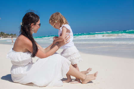 Back view of mother and his little daughter enjoy vacation at tropical beach photo