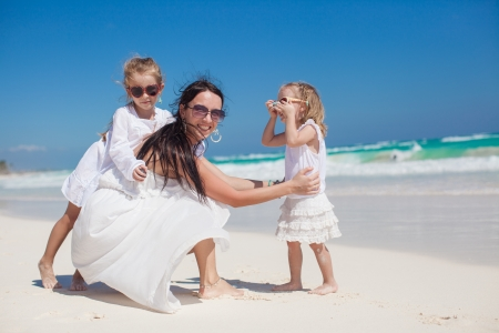 Young mother and two her fashion kids at exotic beach on sunny day photo