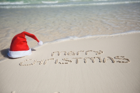 tranquil scene: Merry Christmas written on tropical beach white sand with xmas hat