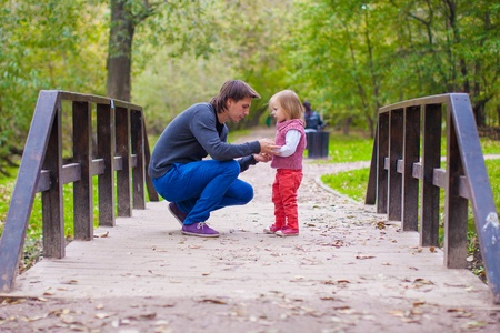 Young father walking with his little daughter in autumn park photo