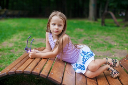 Cute little girl lying on wooden chair and relaxing outdoor in the park photo