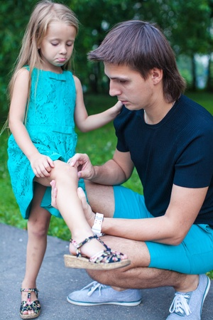 necking: Young father pities his little daughter, who hurt her leg