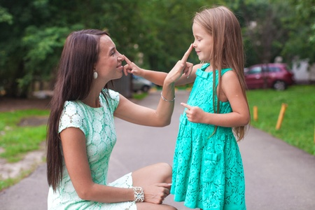 Happy young mother and her daughter having fun outdoors photo