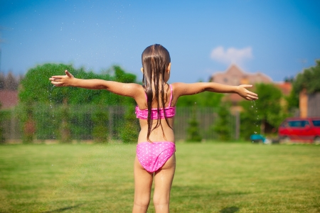 Back view of little girl in a swimsuit playing and splashing in the yard photo