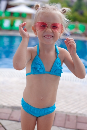Cute little girl standing alone near swimming pool and smiling photo