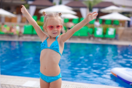 Beautiful little girl spread her arms standing near swimming pool photo