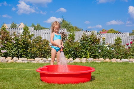 hosepipe: happy little girl pouring water from a hose and laughing