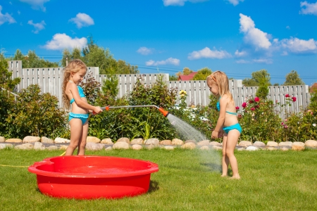 Two little sisters frolicing, splashing and having fun in their yard