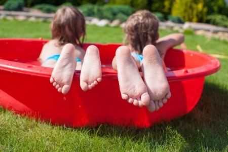 mojar: Primer plano de los pies de dos hermanas en una pequeña piscina