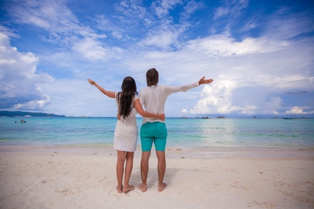 Back view of young couple spread their arms standing on white sandy beach photo