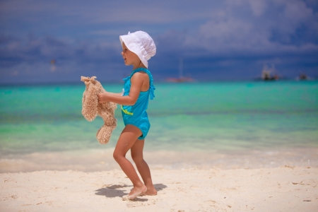 Adorable little girl with her favorite toy on tropical beach vacation photo