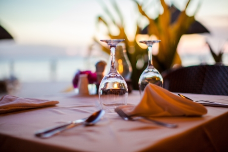 夕暮れセットのテーブルの上のクローズ アップの空ワイン グラス 写真素材