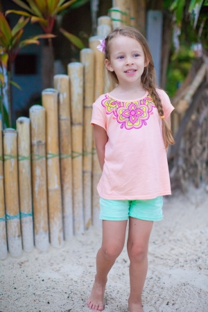 Adorable little girl smiling on tropical beach vacation photo