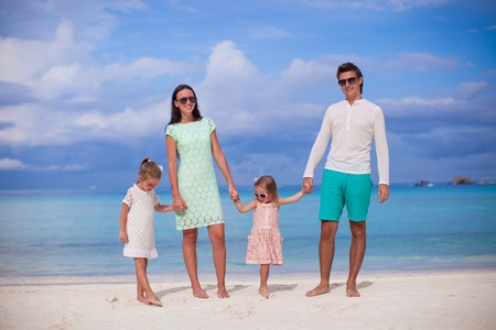 Fashion family of four walking by the sea and enjoy beach vacation photo