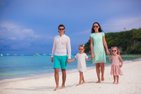Young beautiful family with two kids walking on tropical vacation photo
