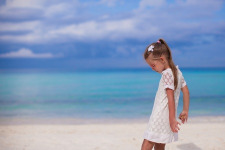 Cute little girl walking on tropical beach vacation photo