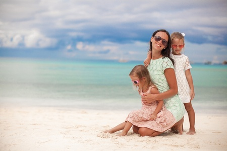 sunny day: Fashion mother and two her adorable daughters at exotic beach on sunny day Stock Photo