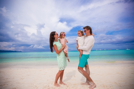 Young beautiful family with two kids looking at each other on tropical vacation photo