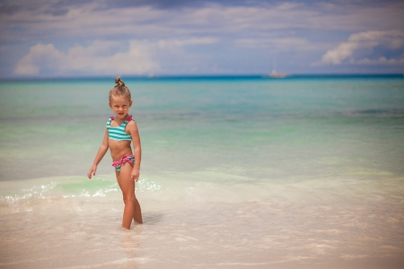 Adorable little girl walking in the water on tropical beach vacation photo