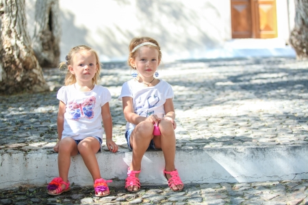 Young charming girls sitting at street in old Greek village of Emporio, Santorini photo