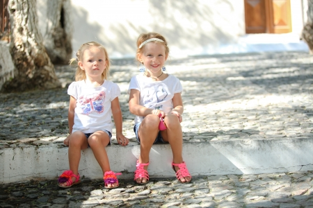 Little cute sisters sitting at street in old Greek village of Emporio, Santorini photo