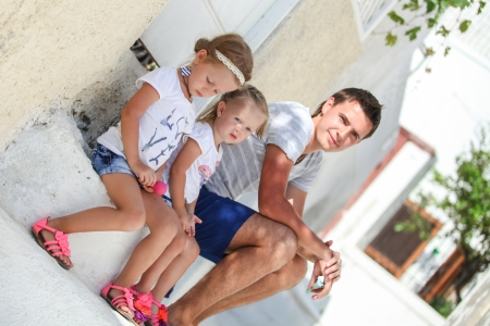 Young father and his daughter sitting on doorstep of old house on street in Emporio, Santorini photo
