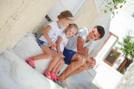 Happy father and cute daughters sitting on street in old greek town photo