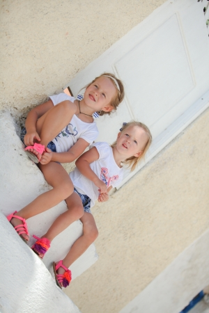 Little cute sisters sitting near old house in Greek village of Emporio, Santorini photo