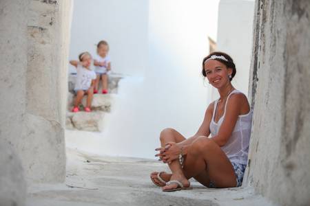 Happy mother background her adorable daughters in a Greek village on the Cyclades Islands photo