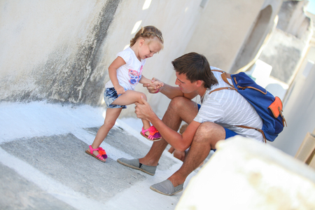 necking: Young father pities his little daughter, who hurt her leg on Greek Street Stock Photo