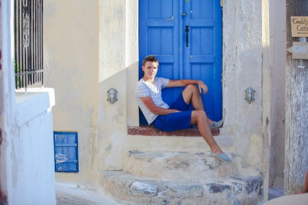 Young man sitting near old blue door of Emporio village on the island Santorini,Greece photo