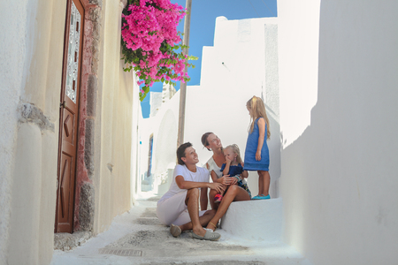 Beautiful family of four sitting on doorstep of old greek house in the street Emporio,Santorini
