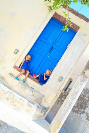 stoep: Two little adorable girls sitting on doorstep of old house in Emporio village, Santorini, Greece